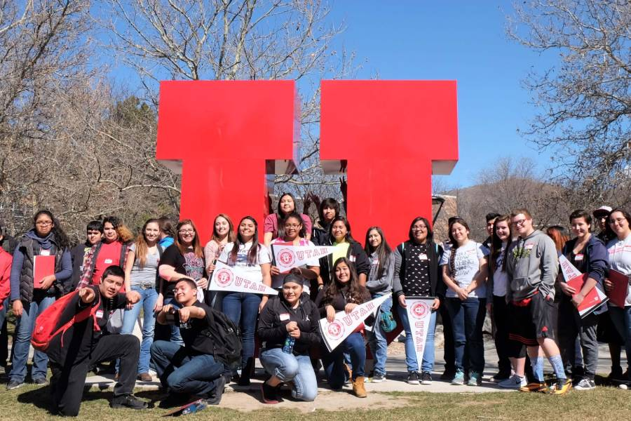 "Students on campus pose in front of large red ""U"""